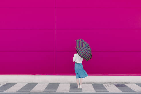 Rear view of young woman with umbrella standing in front of a pink wall - ERRF02815