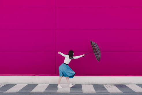 Young woman holding umbrella in front of a pink wall - ERRF02818