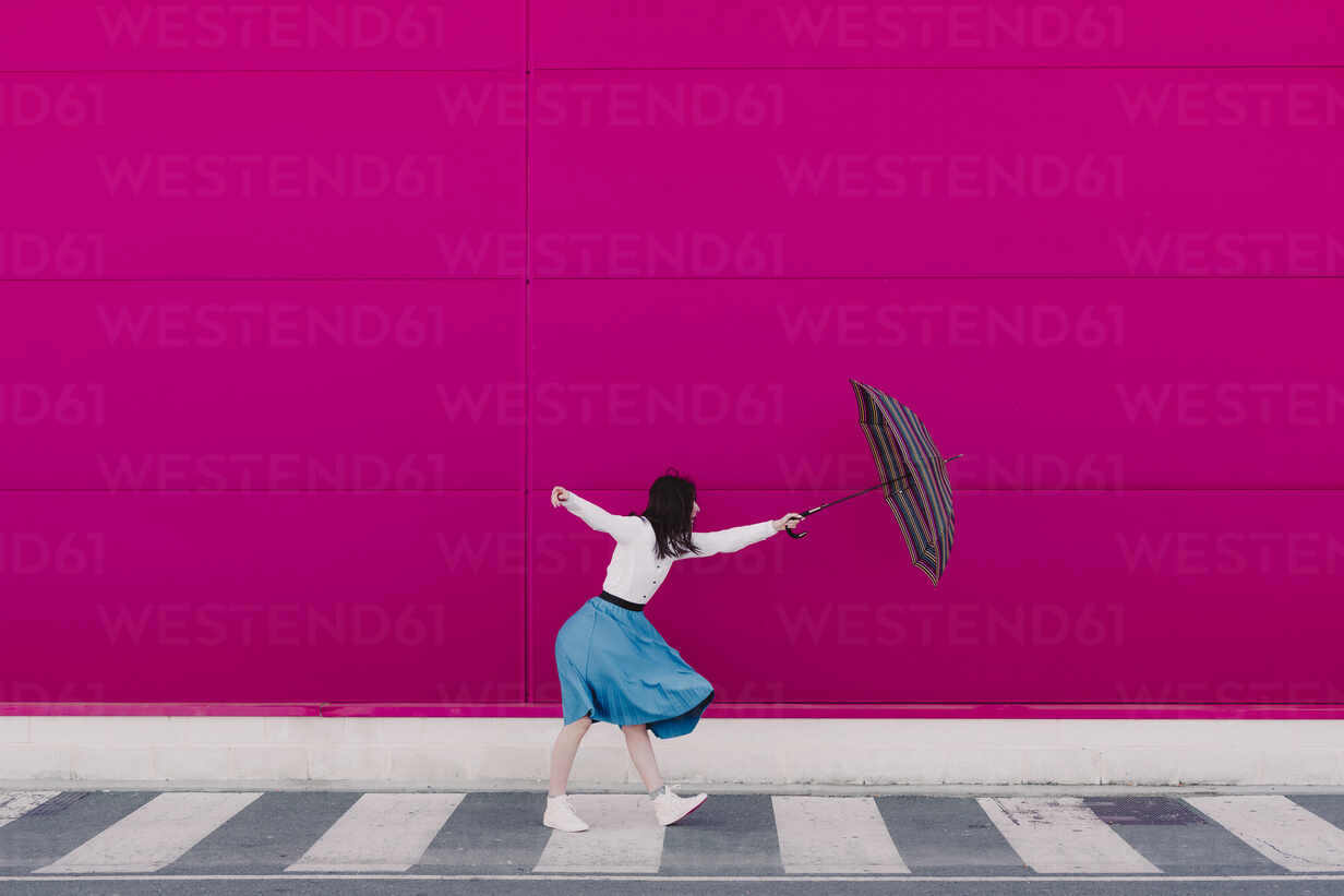 Young woman holding umbrella in front of a pink wall - ERRF02818 - Eloisa Ramos/Westend61