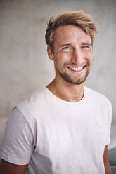 Portrait of happy young man wearing white t-shirt - PNEF02414