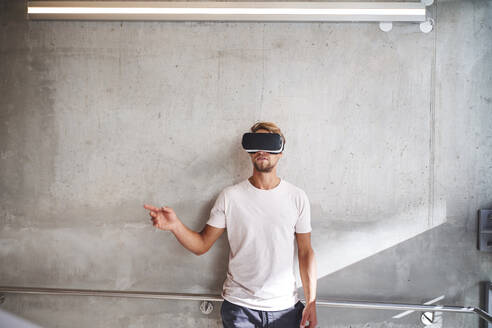 Young man wearing virtual reality goggles - PNEF02417