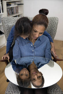 Mirror image of mother and her little daughter sitting together on armchair - PSTF00626
