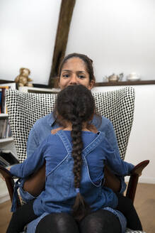 Back view of little girl with long braid sitting on her mother's lap on an armchair - PSTF00632