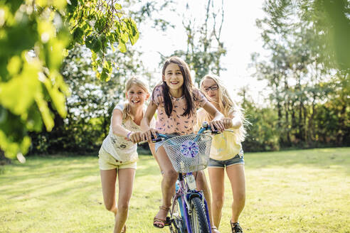 Happy girls riding bicycle in garden - SODF00625