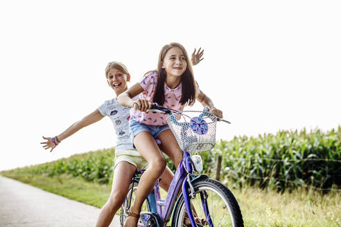 Happy girls riding bicycle on a country lane - SODF00628