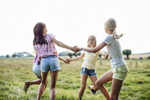 Happy girls dancing on a field together - SODF00634
