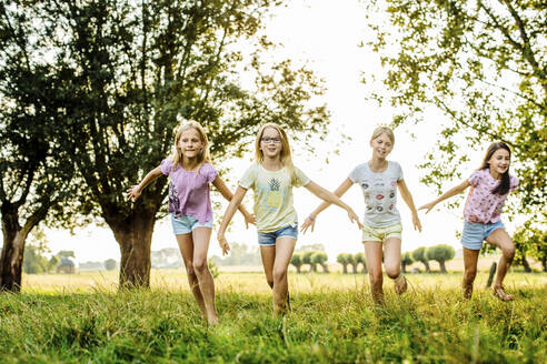 Happy girls running on a field in the countryside - SODF00643