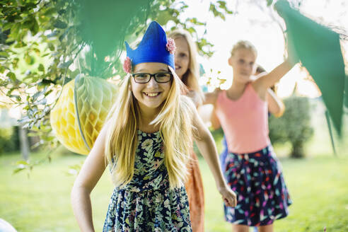 Portrait of happy girl wearing a party hat on a birthday party outdoors - SODF00664