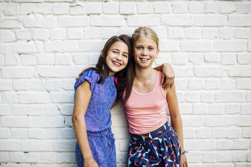 Portrait of two happy girls embracing at a wall - SODF00682