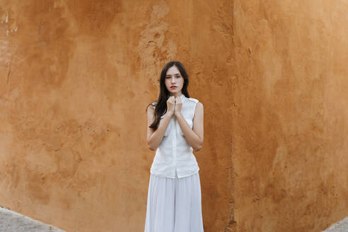 Portrait of female teenager wearing white clothes in front of a brown wall - TCEF00232