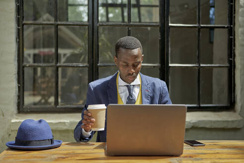 Stylish young businessman wearing old-fashioned suit using laptop at an outdoor cafe - VEGF01605