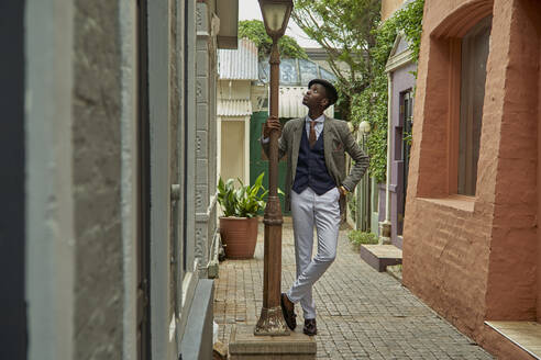 Stylish young businessmann with a beret holding a streetlight in an alley - VEGF01629