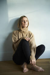 Portrait of thoughtful blond young woman sitting on the floor - PNEF02435