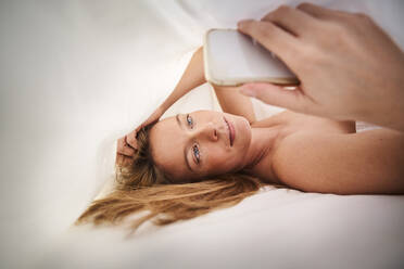 Blond young woman lying in bed under blanket using cell phone - PNEF02444