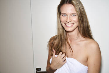 Portrait of happy young woman wrapped in a towel - PNEF02453