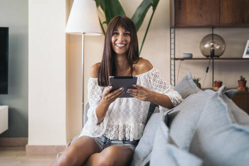 Portrait of smiling young woman sitting on the couch at home using tablet - MPPF00519