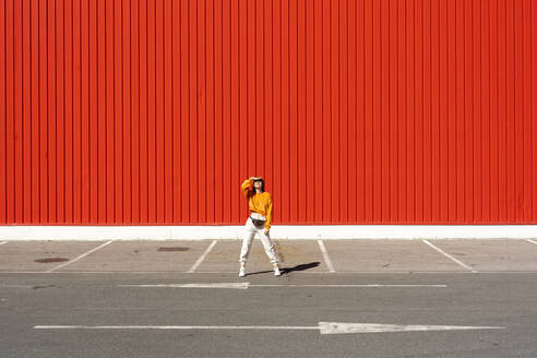 Young woman standing in front of a red wall - ERRF02823