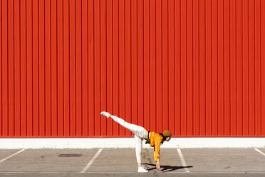 Young woman dancing in front of a red wall - ERRF02826