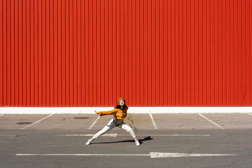 Young woman dancing in front of a red wall - ERRF02829