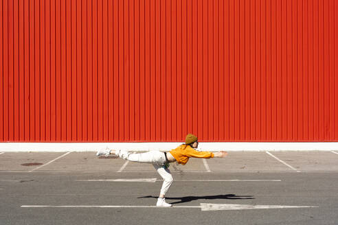 Young woman dancing in front of a red wall - ERRF02832