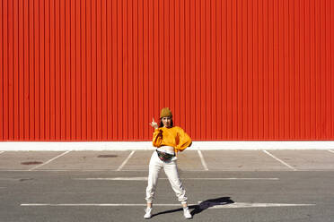Young woman posing in front of a red wall - ERRF02835