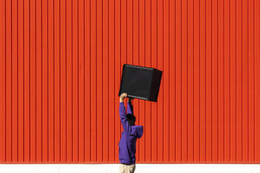 Young man carrying a box in front of a red wall - ERRF02838