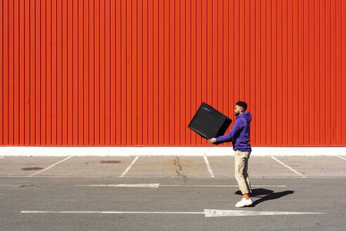 Young man carrying a box in front of a red wall - ERRF02844
