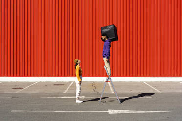 Young man and woman performing with a box in front of a red wall - ERRF02853