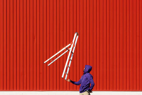 Young man balancing a ladder in front of a red wall - ERRF02862