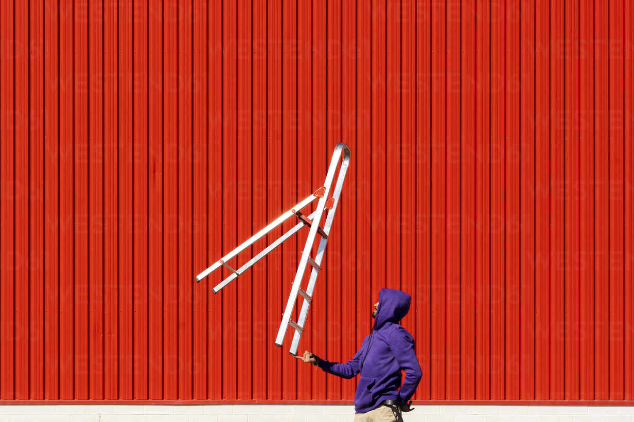 Young man balancing a ladder in front of a red wall - ERRF02862 - Eloisa Ramos/Westend61