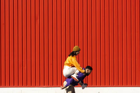 Young man carrying woman piggyback in front of a red wall - ERRF02871