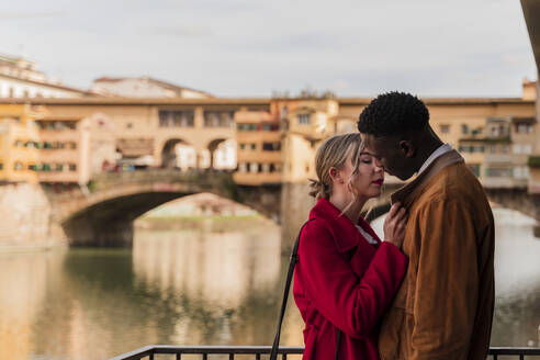 Affectionate young couple kissing in the city of Florence, Italy - FMOF00862