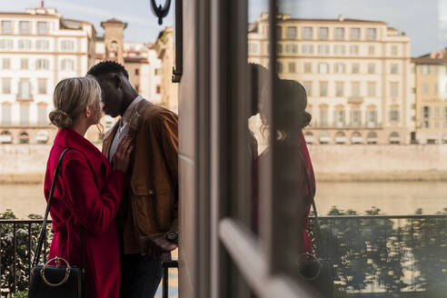 Affectionate young couple kissing in the city of Florence, Italy - FMOF00865