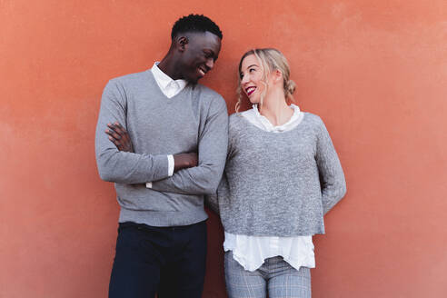 Smiling young couple standing at an orange wall looking at each other - FMOF00871