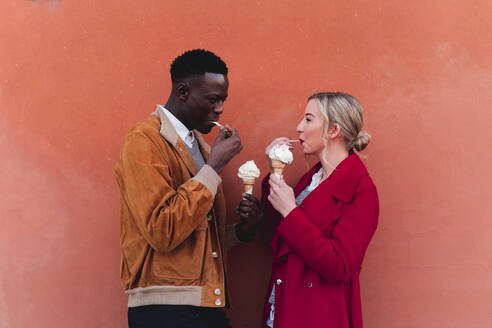 Young couple standing at an orange wall eating ice cream - FMOF00874