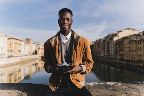 Portrait of smiling young man with a camera on a bridge above river Arno, Florence, Italy - FMOF00883