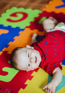 Portrait of smiling baby boy lying on colourful flooring - LJF01371