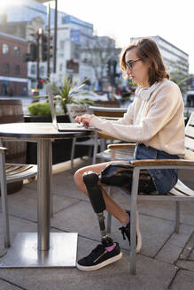 Young woman with leg prosthesis sitting in a sidewalk cafe in the city using laptop - FBAF01281