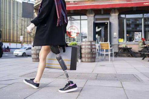 Low section of woman with leg prosthesis walking in the city - FBAF01284