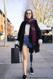 Portrait of confident young woman with leg prosthesis walking in the city - FBAF01287