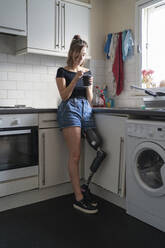 Young woman with leg prosthesis drinking coffee in kitchen at home - FBAF01296