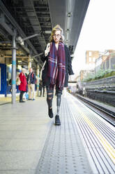 Young woman with leg prosthesis walking at station platfom - FBAF01299
