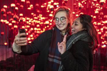 Portrait of happy friends taking a selfie in front of red light bulbs - FBAF01314