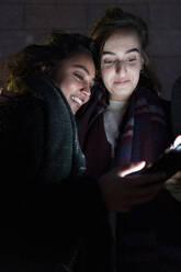 Friends looking at illuminated smartphones in the dark - FBAF01317