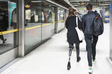 Rear view of young woman with leg prosthesis and man walking at subway station platfom - FBAF01323