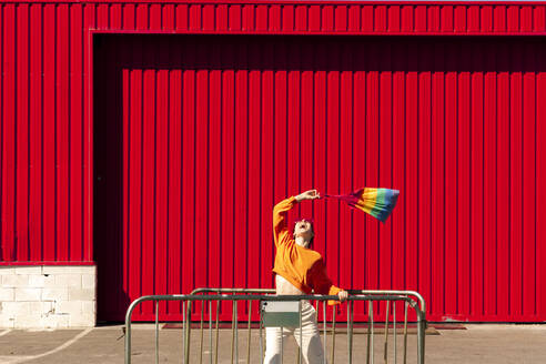 Lesbian with colorful bag and a barrier in front of a red wall - ERRF02872