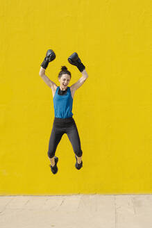 Young female boxer jumping in front of a yellow wall - JCZF00025