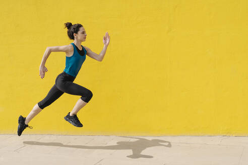 Young woman jogging in front of a yellow wall - JCZF00028