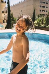 Smiling shirtless boy enjoying by swimming pool in resort - MASF16785