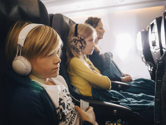 Caucasian boy with headphones sitting with sister and mother in airplane - MASF16794